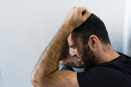 Bearded depressed man standing near white wall  and holding hands on head