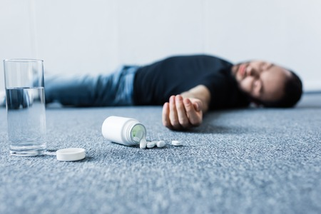 Selective focus of unconscious man lying on grey floor near glass of water and container with pills