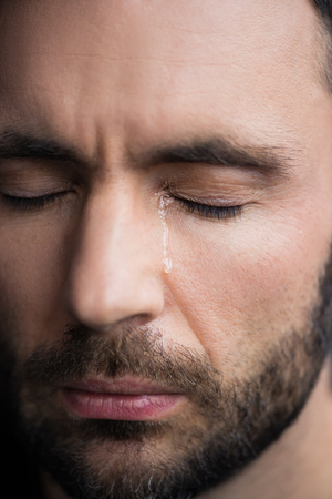 Portrait of handsome depressed man crying with closed eyes