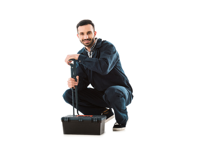 Cheerful  plumber holding adjustable wrench while sitting near toolbox and smiling at camera isolated on white background