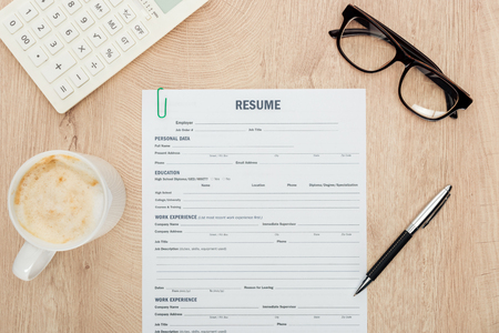 Top view of glasses, pen, calculator, cup of cappuccino and resume template on wooden surface