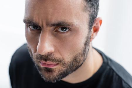 Retrato de hombre barbudo serio y guapo mirando a la cámara