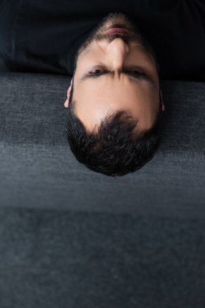 Overhead view of short haired depressed man lying on grey sofa at home