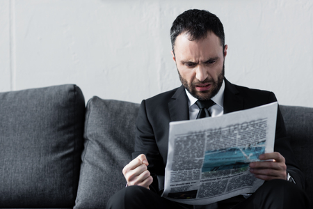 Bearded worried businessman reading newspaper while sitting on sofa
