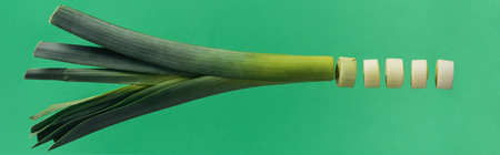 Panoramic shot of chopped green nutritious leek isolated on green background