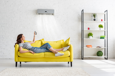 Attractive young girl lying on yellow sofa under air conditioner at home