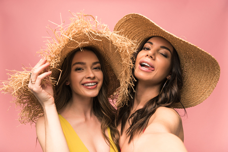 Two smiling girls in straw hats taking selfie isolated on pink background