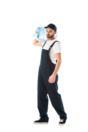 Serious delivery man in overalls carrying bottle of water isolated on white background