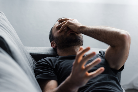 Depressed man suffering while lying on sofa and holding hand on face Stock fotó