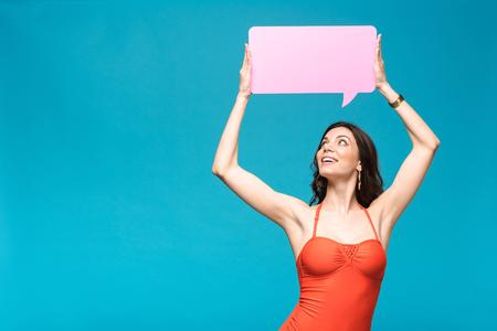 Charming girl in swimsuit holding speech bubble isolated on blue background Reklamní fotografie