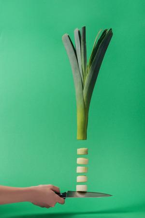 Vue recadrée d'une femme tenant un couteau avec un poireau tranché vert sur fond vert