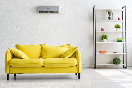 Spacious living room with air conditioner on white wall, yellow sofa and rack