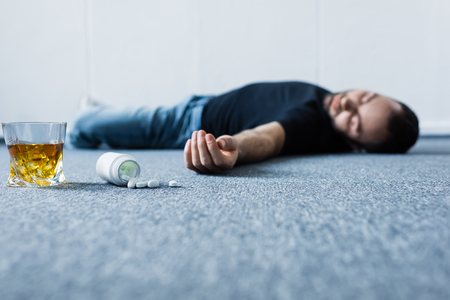 Selective focus of adult unconscious man lying on grey floor near containers with pills and glass of whiskey