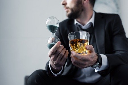Partial view of adult man in suit holding hourglass and glass of whiskey Stockfoto