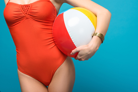 Cropped view of woman in swimsuit holding inflatable beach ball isolated on blue background Stock Photo