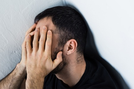 Depressed man sitting in corner and covering face with hands