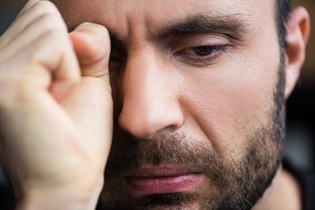 Portrait of handsome crying man wiping tears away with hand