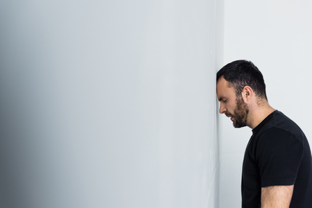 Handsome depressed man standing by white wall with closed eyes Reklamní fotografie