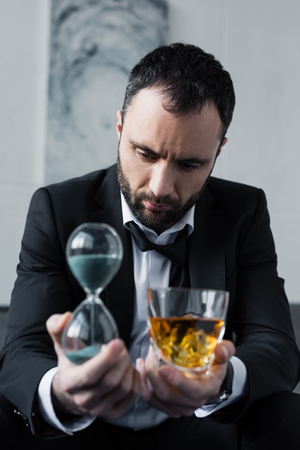 Selective focus of depressed businessman holding glass of whiskey and hourglass 免版税图像