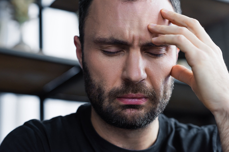 Sad unshaven man holding hand near head with closed eyes