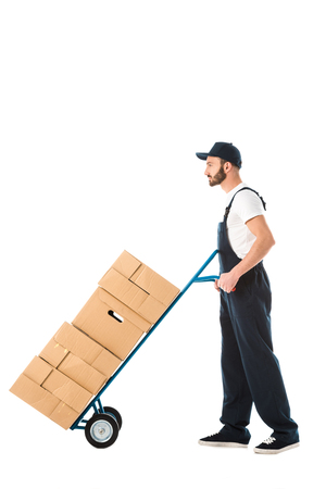 Serious delivery man transporting hand truck loaded with cardboard boxes isolated on white background Stock Photo