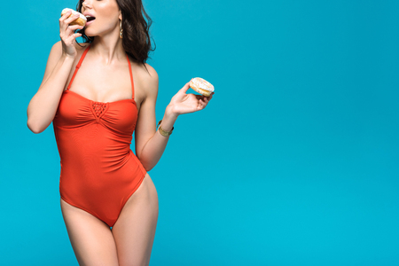 Cropped view of woman in swimsuit eating donuts isolated on blue background