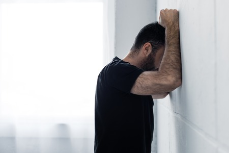 Adult depressed man in black t-shirt suffering while standing near white wall