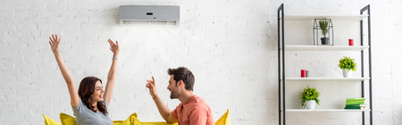 Panoramic shot of excited man and woman sitting under air conditioner at home