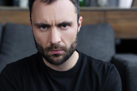 Grave apuesto hombre barbudo en camiseta negra mirando a la cámara