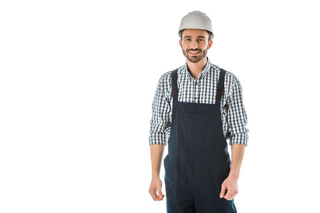 Smiling construction worker in overalls and helmet looking at camera isolated on white background