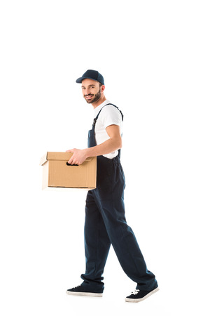 Handsome smiling delivery man carrying cardboard box and looking at camera isolated on white background