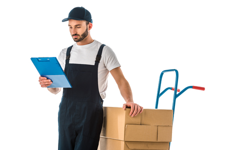 Serious delivery man looking at clipboard while standing near hand truck loaded with cardboard boxes isolated on white background
