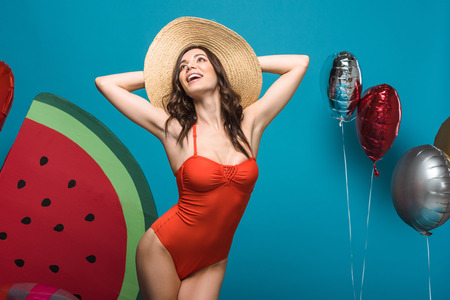 Excited woman in swimsuit and straw hat with balloons on blue background