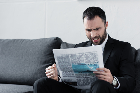 Handsome irritated business sitting on sofa and reading newspaper