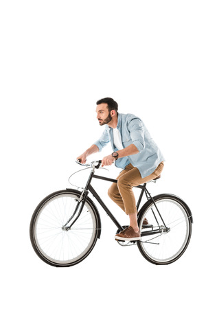 Handsome bearded man riding bicycle and looking ahead isolated on white background