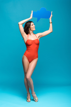 Full length view of pretty girl in swimsuit holding thought bubble on blue background Reklamní fotografie