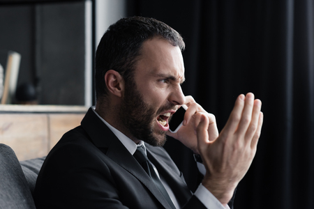 Angry bearded businessman quarreling while talking on smartphone in office