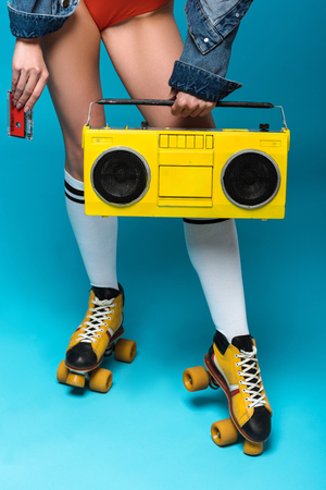 Cropped view of woman in swimsuit and roller skates holding boombox and cassette tape on blue background