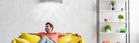 Scatto panoramico di un bell'uomo seduto sul divano giallo sotto il condizionatore d'aria a casa