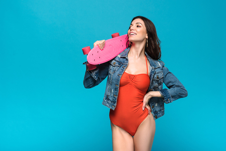 Pretty girl in swimsuit and denim jacket holding longboard isolated on blue background