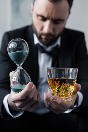 Selective focus of upset businessman holding hourglass and glass of whiskey