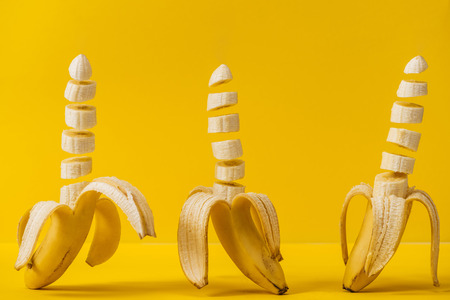 Fresh delicious sliced bananas isolated on yellow background Stock Photo
