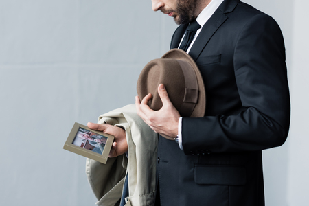 Partial view of man in suit holding hat in hand while looking at photo in frame 免版税图像