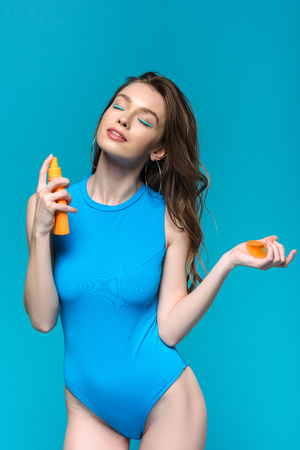 Smiling girl in swimsuit applying sunscreen with closed eyes isolated on blue background Reklamní fotografie
