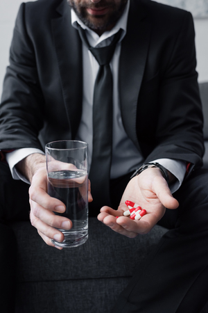 Partial view of depressed man holding glass of water and handful of pills