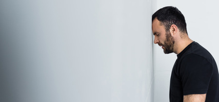 Panoramic shot of depressed bearded man standing by white wall with closed eyes