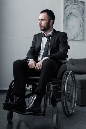 Pensive disabled man in black suit sitting in wheelchair and looking away Stock fotó