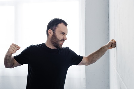 Angry bearded man in black t-shirt kicking white wall with hand 版權商用圖片