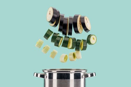 Sliced fresh organic vegetables above saucepan isolated on turquoise background