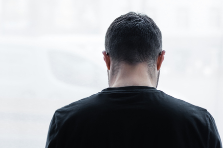 Back view of lonely short haired man standing by window at home